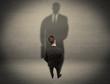 Businessman looking at big shadow concept