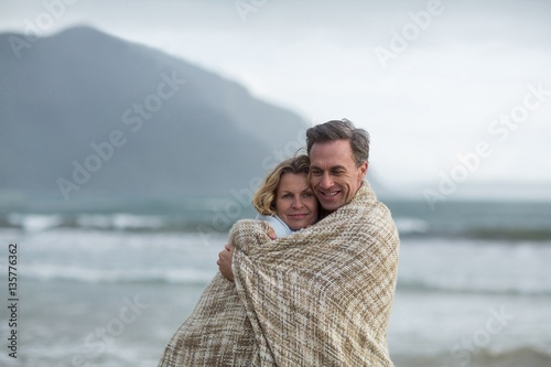 Fotografia, Obraz  Mature couple wrapped in blanket on the beach