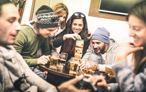 Fototapeta Happy friends playing table board game while drinking beer at pub - Cheerful people having fun at brewery bar corner - Friendship concept on contrast desaturated filter with soft greenery color tones obraz