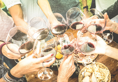 Fotografía  Friends hands toasting red wine glass and having fun outdoors cheering with wine