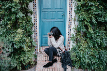 Young Woman Taking Pictures Sitting Besides A Blue Door