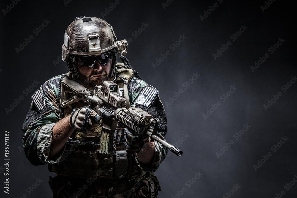 Fototapeta United states Marine Corps special operations command Marsoc raider with weapon. Studio shot of Marine Special Operator half-turning black background