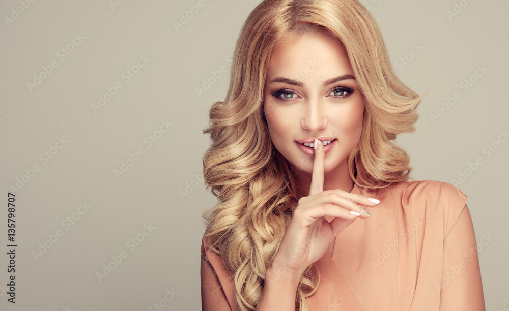 Fototapeta Beautiful girl blonde hair with an elegant hairstyle  holding a finger to her mouth with a secret .Woman with hair wavy ,curly hairstyle .
