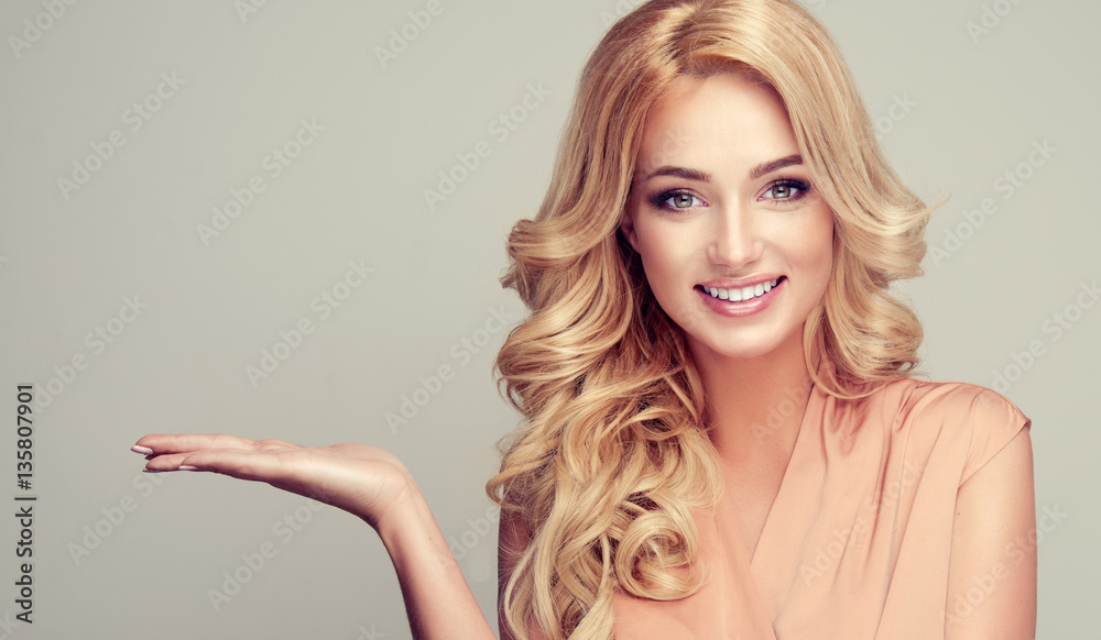 Fototapeta      Blonde woman with curly hair shows your product . .Beautiful girl with beautiful smile pointing to the side . Presenting your product. Expressive facial expressions