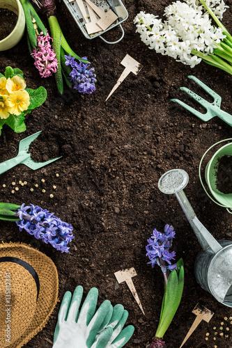 Papiers peints Jardin Spring garden works. Gardening tools and flowers on soil.