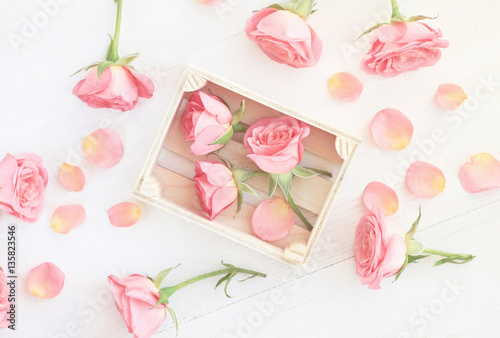 Little Light Pink Roses In Wooden Box And Petals Tered Over Table Soft White
