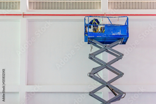 Photo  Scissor lift platform with hydraulic system elevated towards a factory roof with