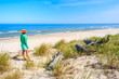 Young woman standing on white sand and looking at beautiful beach, Baltic Sea, Poland