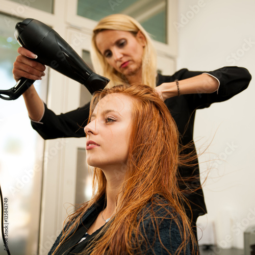 Stylist drying hair of a female client at the beauty salon - hai