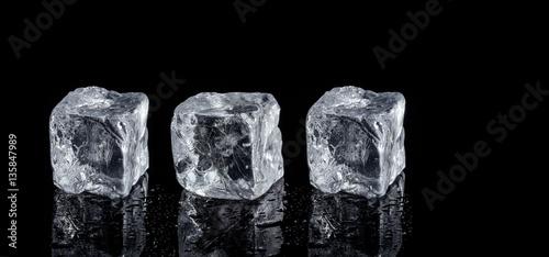 three ice cubes on black background