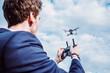 canvas print picture - Mann fliegt Drohne/Drohnenpilot im Anzug