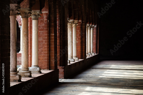 Tableau sur Toile Light and shadows over the colonnade of a romanesque cloister in an italian medi