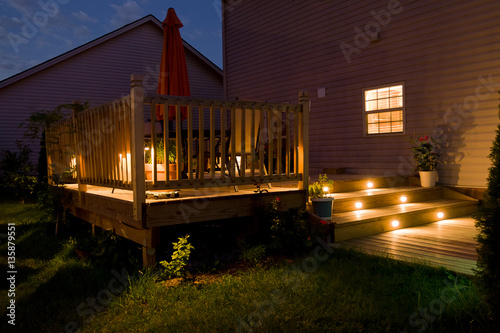 Stampa su Tela Wooden deck and patio of family home at night.