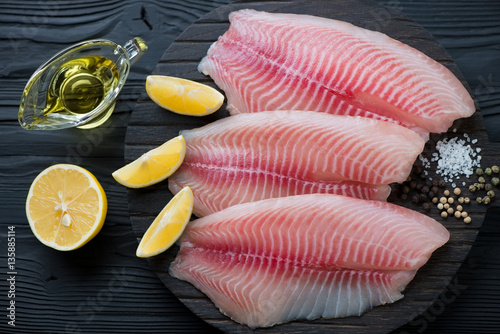 Raw fresh tilapia fillets with seasonings ready to be cooked Canvas Print