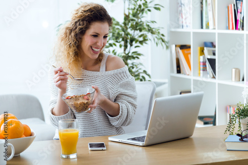 Fotografía Beautiful young woman working with laptop while eating at home.