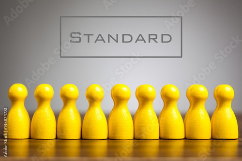 Stampa su Tela Standard concept with pawn figurines on table, grey background