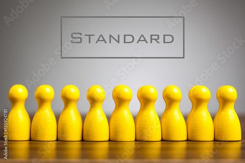 Foto Standardkonzept mit Pfandfigürchen auf Tabelle, grauer Hintergrund
