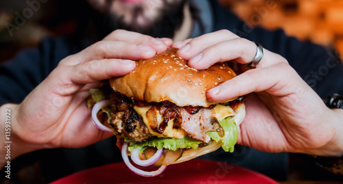 Tablou Canvas Young man eating a cheeseburger.