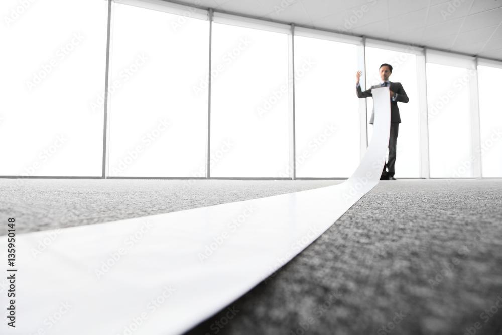 Fototapety, obrazy: Office worker unrolling long sheet