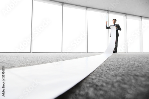 фотография  Office worker unrolling long sheet