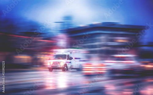 Fotografía an ambulance racing through the rain on a stormy night with motion blur