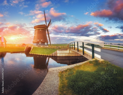 Tuinposter Molens Windmill and bridge near the water canal at sunrise in Netherlands. Traditional dutch windmill against colorful sky in dusk. Spring landscape in Holland. Sunny morning. Cloudy sky reflected in water
