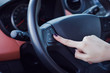 Woman push the button on a steering wheel in car