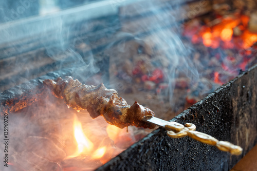 Valokuva  Spit roasted meat on a charcoal grill