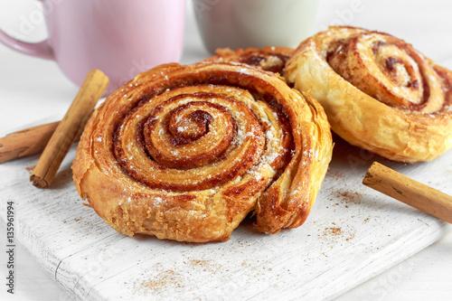Foto op Plexiglas Bakkerij Freshly Baked Traditional Sweet Cinnamon Rolls, Swirl on white wooden board