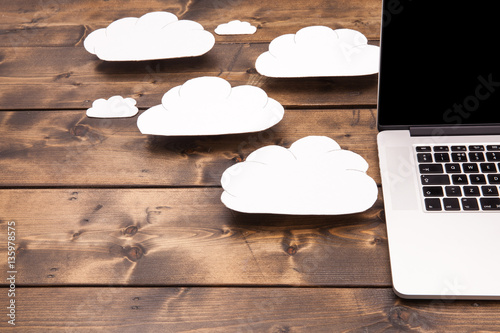 Cloud computing concept laptop close up with white clouds coming out of the computer indicating online storage and internet connection.