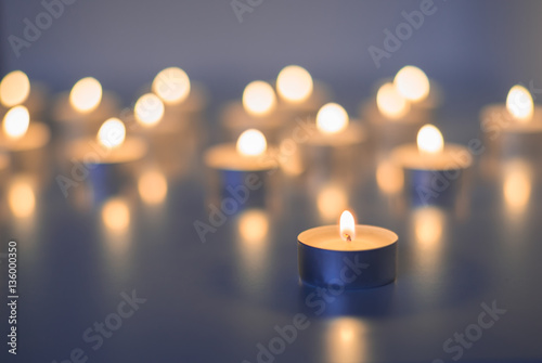 obraz lub plakat Flame of many candles burning on the background blue color