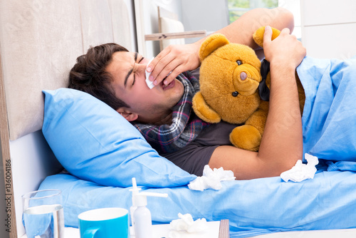 Fotografia  Sick man with flu lying in the bed