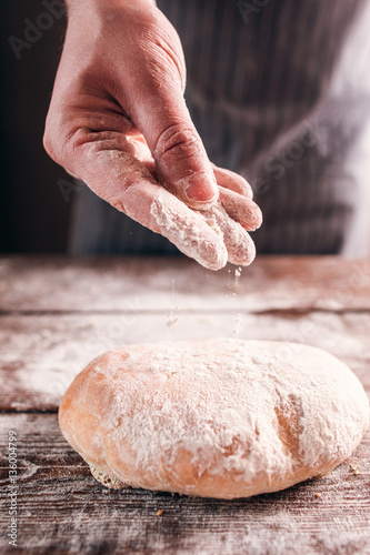 Deurstickers Bakkerij Baker hand sprinkle flour on fresh bun close-up. Man finishing his pastry, decorating warm bread with sugar powder. Traditional rustic recipe, homemade bakery concept