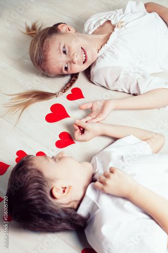 Fotografering  little boy and girl lying on the floor.