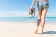 Young woman with sandals walking on beach