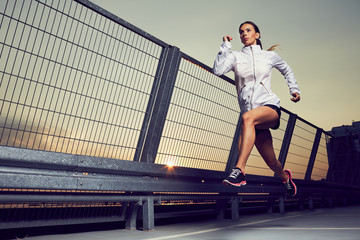 Fototapeta Athletic woman running during sunset on rooftop of parking, garage