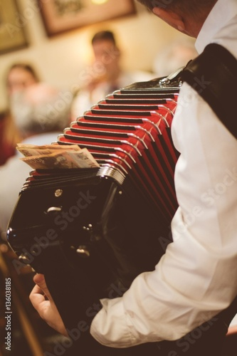 Vászonkép  Man playing accordion in serbian bar
