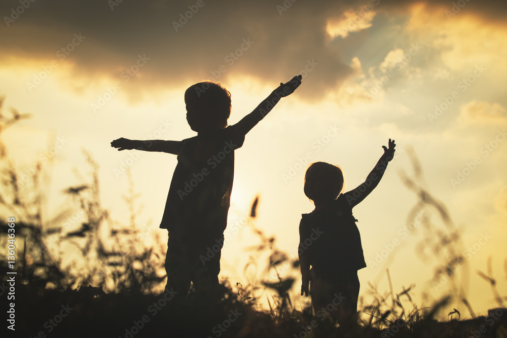 Fototapety, obrazy: little boy and girl silhouettes play at sunset