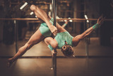 Beautiful woman performing pole dance on pole