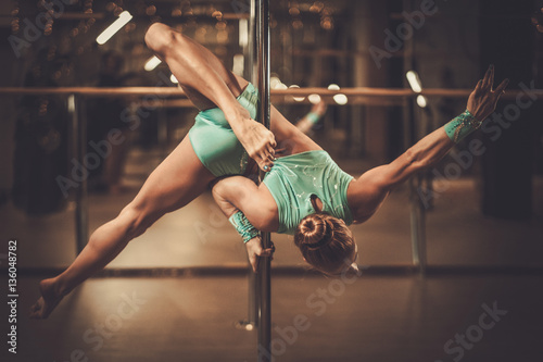 Fotografie, Obraz  Beautiful woman performing pole dance on pole