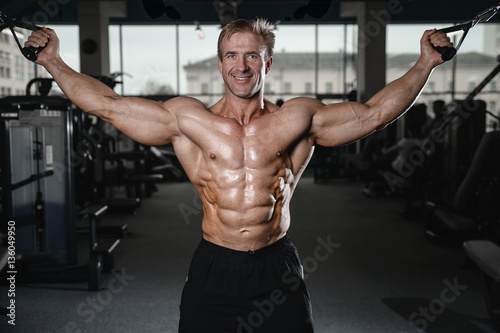 Fotografiet  Brutal strong bodybuilder man pumping up muscles and train gym