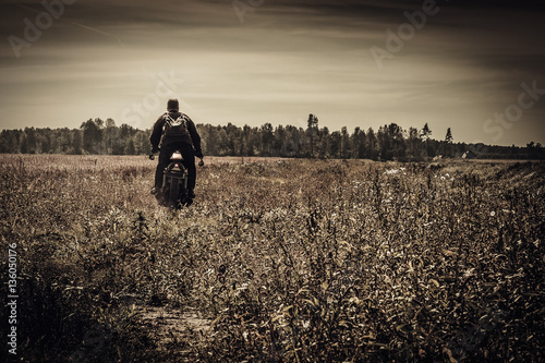 Stampa su Tela Young, stylish man on vintage custom racer in field