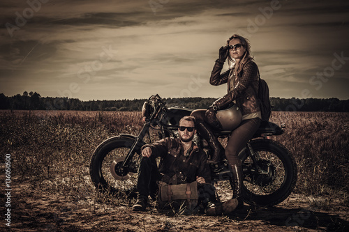 Young, stylish cafe racer couple on vintage custom motorcycles in field Wallpaper Mural