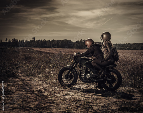 Fotografija Young, stylish cafe racer couple on vintage custom motorcycles in field
