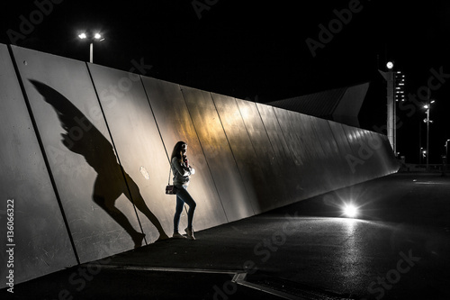 Conceptual photo of silhouette of young woman standing next to the wall at night. There is a big shadow on the wall, Barcelona, Spain