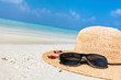Sun hat and sunglasses on sand, clear turquoise ocean in Maldives.
