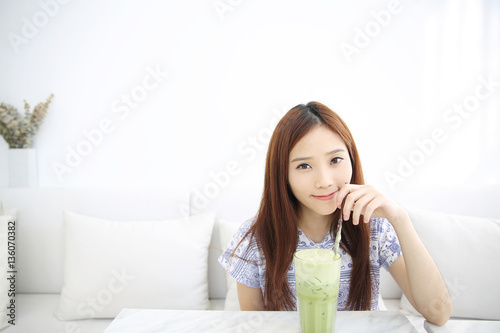 47710f558 Asian young woman drinking Iced green tea latte in white coffees ...