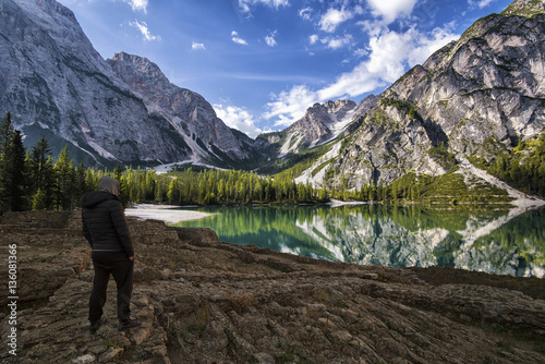 Poster Bergen man standing watching the mountains in front of a pond