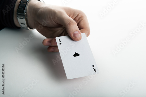 Human hand holding the ace of spades плакат