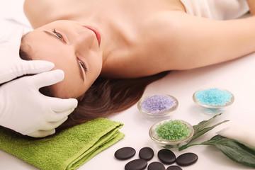 Obraz na płótnie Canvas Spa. Care Facial. Beauty young woman gets a head massage in the salon